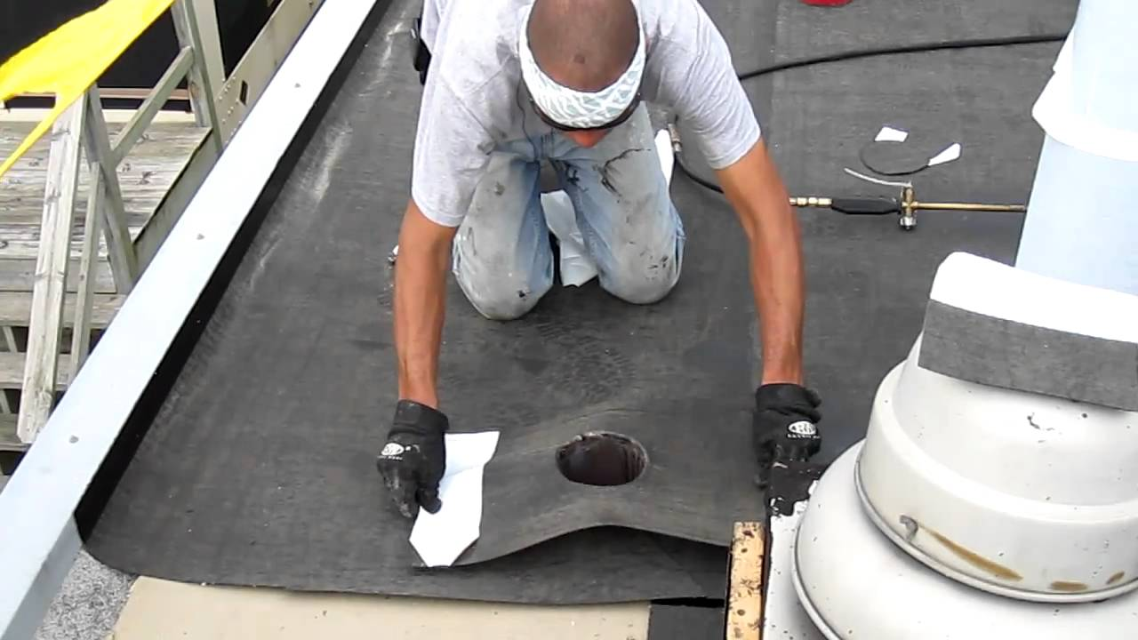 Great Lakes Roofing Technician Applies Flashing To Roof