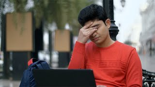 Young college student suffering from a severe headache - health and medical concept