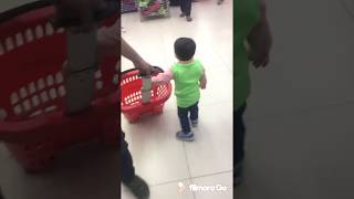 Funny baby doing shopping in the supermarket.