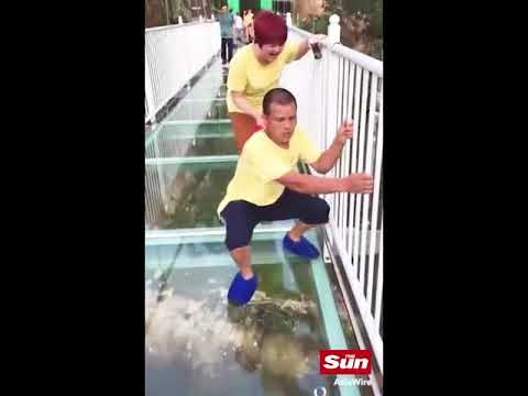 Dramatic moment tour guide collapses in terror as a glass walkway cracks beneath his feet