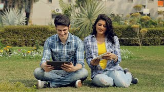 Young happy couple playing games on tablet sitting outside in a park on a bright sunny day