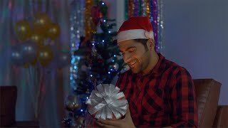 Happy Indian guy opens his magical Christmas present during Christmas celebration in India