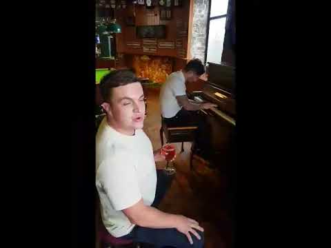 Two lads have a singalong in a pub