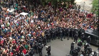Tensions high as police hold back people outside Barcelona polling stations