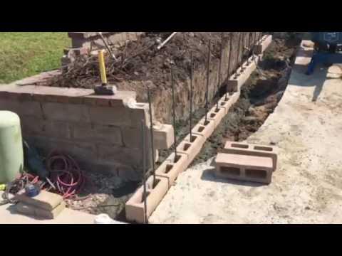 Short retaining block wall preparation by crown for Slump block construction