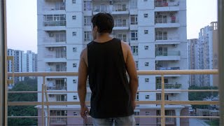 Muscular Indian young man walks outside of his bedroom to the balcony