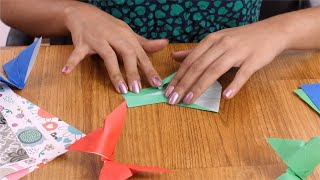 Shot of a girl making origami dress from a green colour craft paper