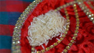 Closeup shot of a girl picking up raw rice from pooja thali