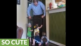 Happy quadruplets preciously greet their dad