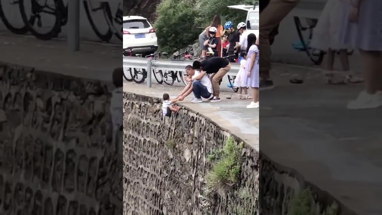 家长把孩子挂在峭壁上拍照