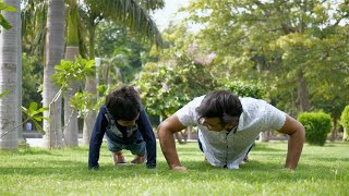 Indian father teaching his young son how to do pushups in a park for a healthy lifestyle
