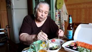 Бабушка ест суши.