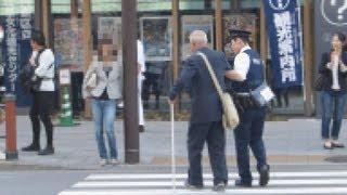 優良警官お年寄りの横断を手助けする警察官。The very kind policeman who helps an old person.
