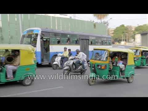 Cubbon Park Metro Station and three-wheeler auto rickshaw drive through traffic in Bangalore