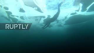Snow joke! Extreme swimmer dives 26m under Baikal ice in nothing but trunks