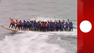 بالفيديو: 66 شخصاً يركبون الأمواج على لوح واحد