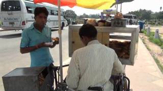 Handicap guy selling  patties on his cycle rickshaw.