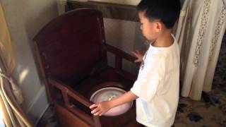 Boy sitting on an antique toilet