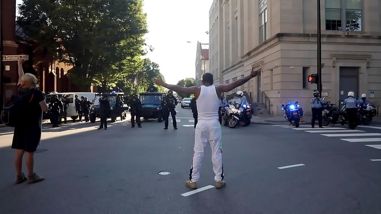 Raleigh police lob the first gas canister at Sunday's protest