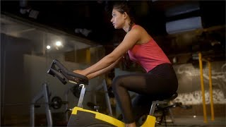 Young female athlete in sportswear pedaling on a spinning bike in the morning