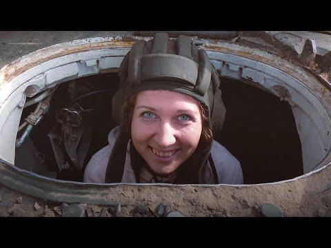 Девушка учится водить танк
