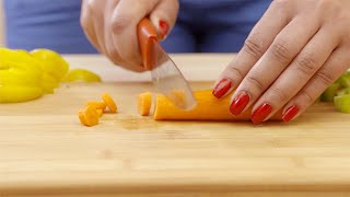 Close up shot of a girl's hands chopping a carrot