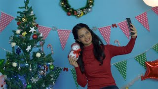 Pretty Indian girl clicking selfies with a small toy snowman during Christmas season