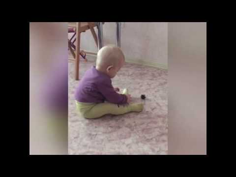 Цепленков Данила учится хватать руками мелкие предметы. Шишка в руках ребенка.