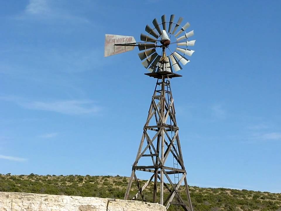 old windmills still at work near giant wind generator