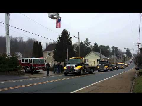 Tow truck funeral procession carries custom-made casket to cemetery