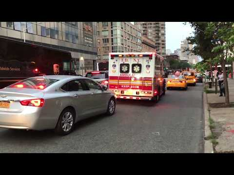 FDNY EMS RESPONDING WITH A UNMARKED NYPD CRUISER IN TOW ON 10TH AVENUE IN MANHATTAN, NEW YORK CITY.
