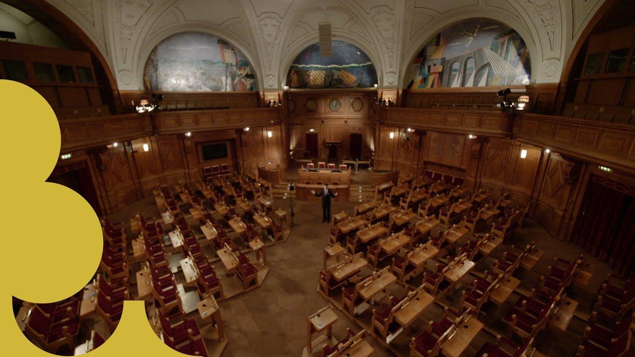 Talman Andreas Norlén står i riksdagens förstakammarsal.