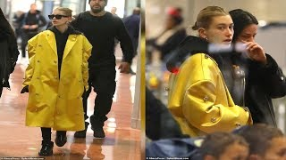 Hailey Baldwin is a ray of sunshine in bright yellow raincoat touching down at Paris airport