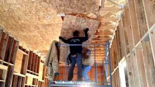 Hanging OSB plywood on a high ceiling a scaffold and two people.