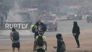 Chile: Protesters collect tear gas canisters in water jugs during clashes with police