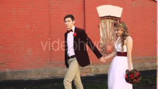 Bride and Groom Walking Along a Brick Red Wall