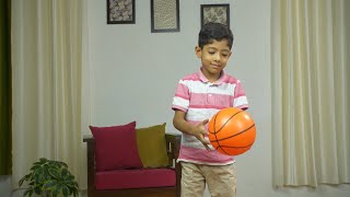 Young Indian kid playing with a basketball at home - evening playtime