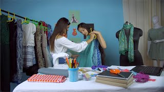 Indian fashion entrepreneur showing different designer dresses to a client at her fashion retail store