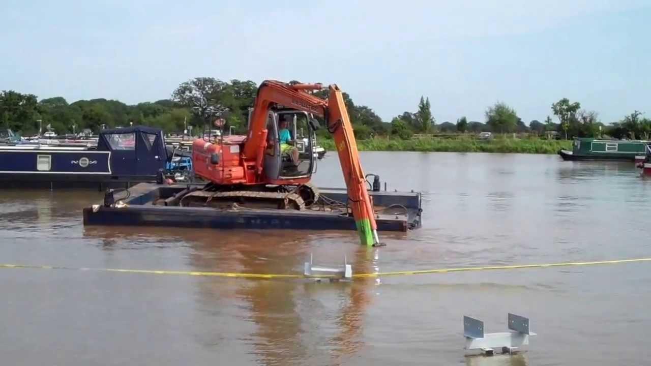 Long reach excavator on small floating pontoon