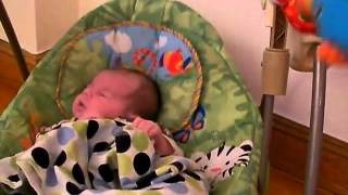 Grayson Danger baby sleeping in Fisher Price swing Casey Cocker Spaniel watching