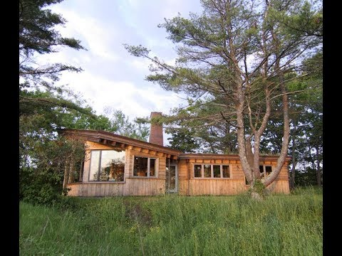 IRREGULAR SHAPED WOODEN HOUSE DESIGN WITH SHALLOW PITCH AND FLAT ROOFS