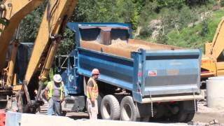 Blue Kenworth Dump Truck dumping dirt on a road construction site
