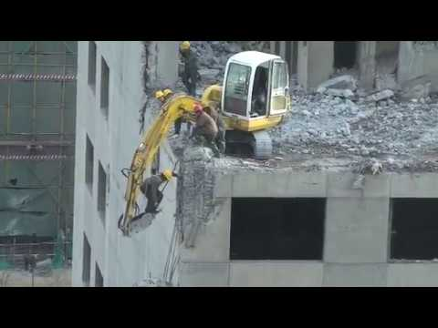 Beijing worker risks his life to demolish part of a building
