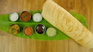 Zoom out shot of South Indian dish masala dosa served over a fresh banana leaf