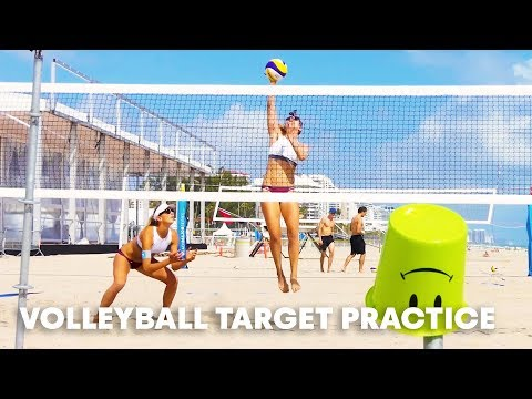 Two beach volleyball players try target practice.