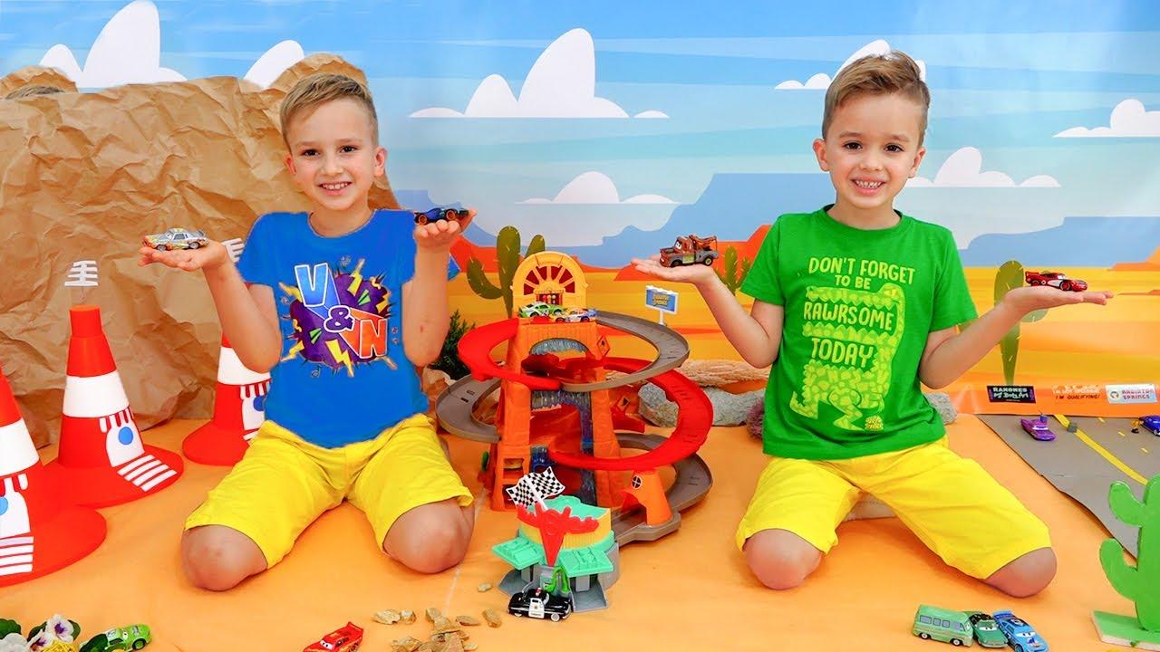 Vlad und Niki spielen mit Spielzeugautos und bauen Speedway-Strecke
