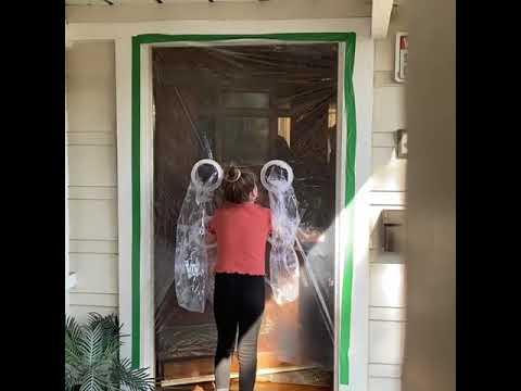 Niña abraza a sus abuelos por cortina de plástico