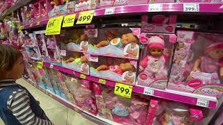 Амелька вибирає іграшки у дитячому магазині.