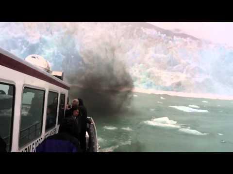 קרחון נופל ליד סירה קטנה