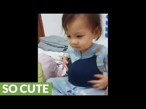 Baby attempts to drink milk from mom's bra